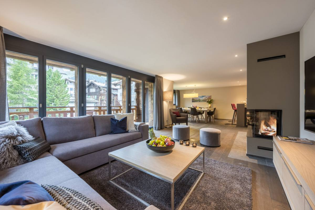 Open-plan living area with balcony access at Christiania Apartment 7 in Zermatt