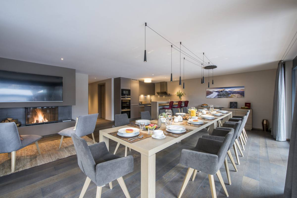 Dining table set for breakfast and open-plan modern kitchen at Christiania Apartment 7 in Zermatt