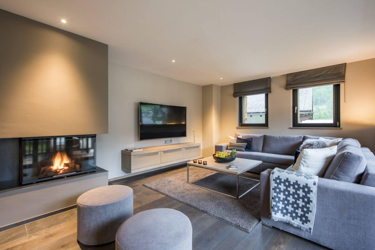 Sofas set around the modern fireplace at Christiania Apartment 7 in Zermatt
