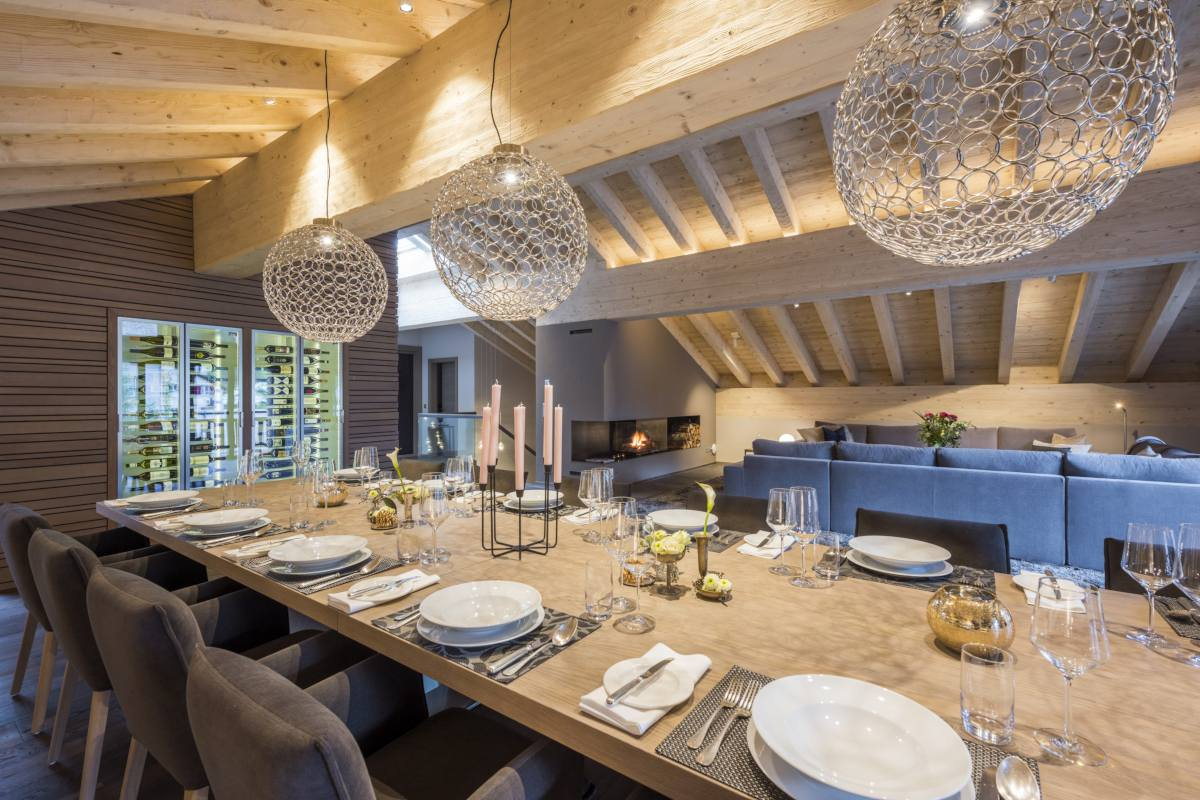 Dining table set for dinner with adjacent wine cellar at Christiania Penthouse in Zermatt