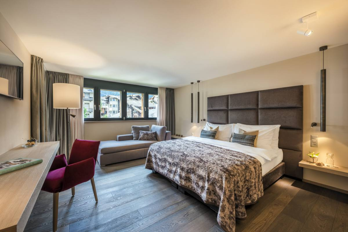 Double/twin bedroom with desk and sitting area at Christiania Penthouse in Zermatt