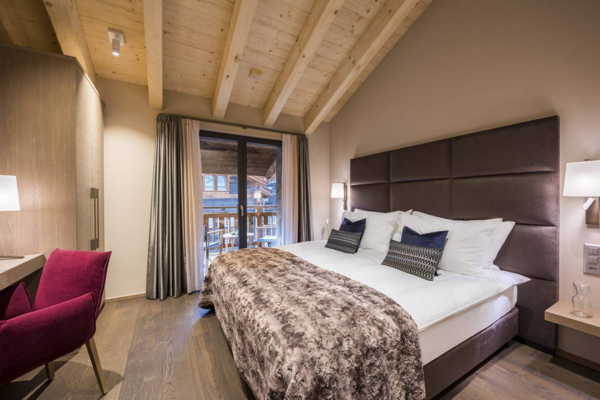 Double/twin bedroom with desk and balcony access at Christiania Penthouse in Zermatt