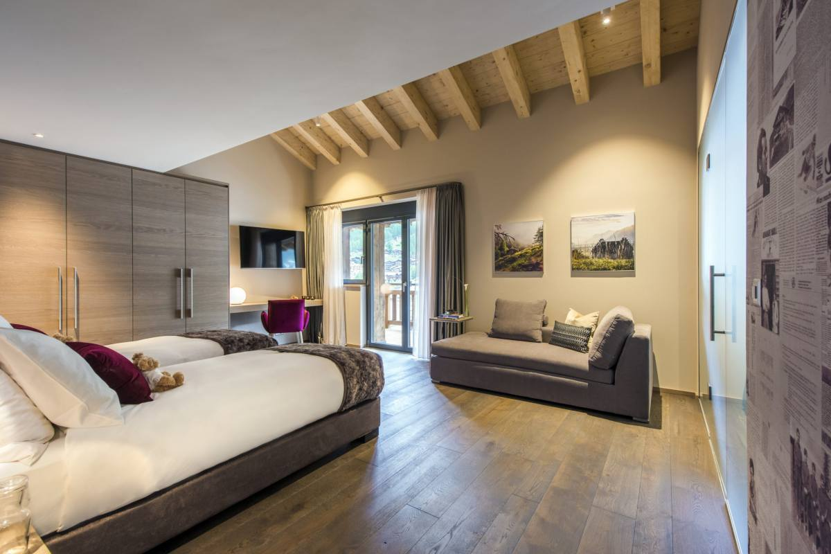 Double/twin bedroom with sitting area and balcony access at Christiania Penthouse in Zermatt