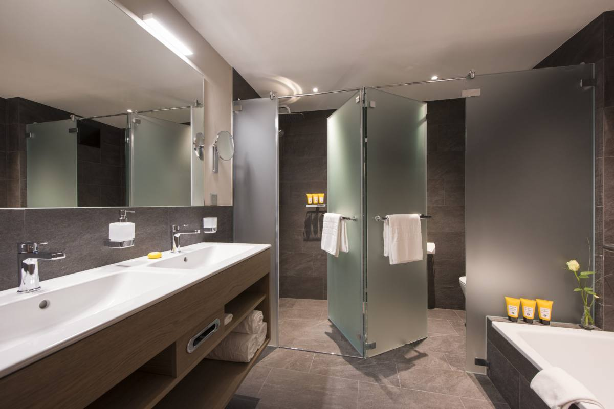 Master bathroom with double shower, double sinks and bathtub at Christiania Penthouse in Zermatt