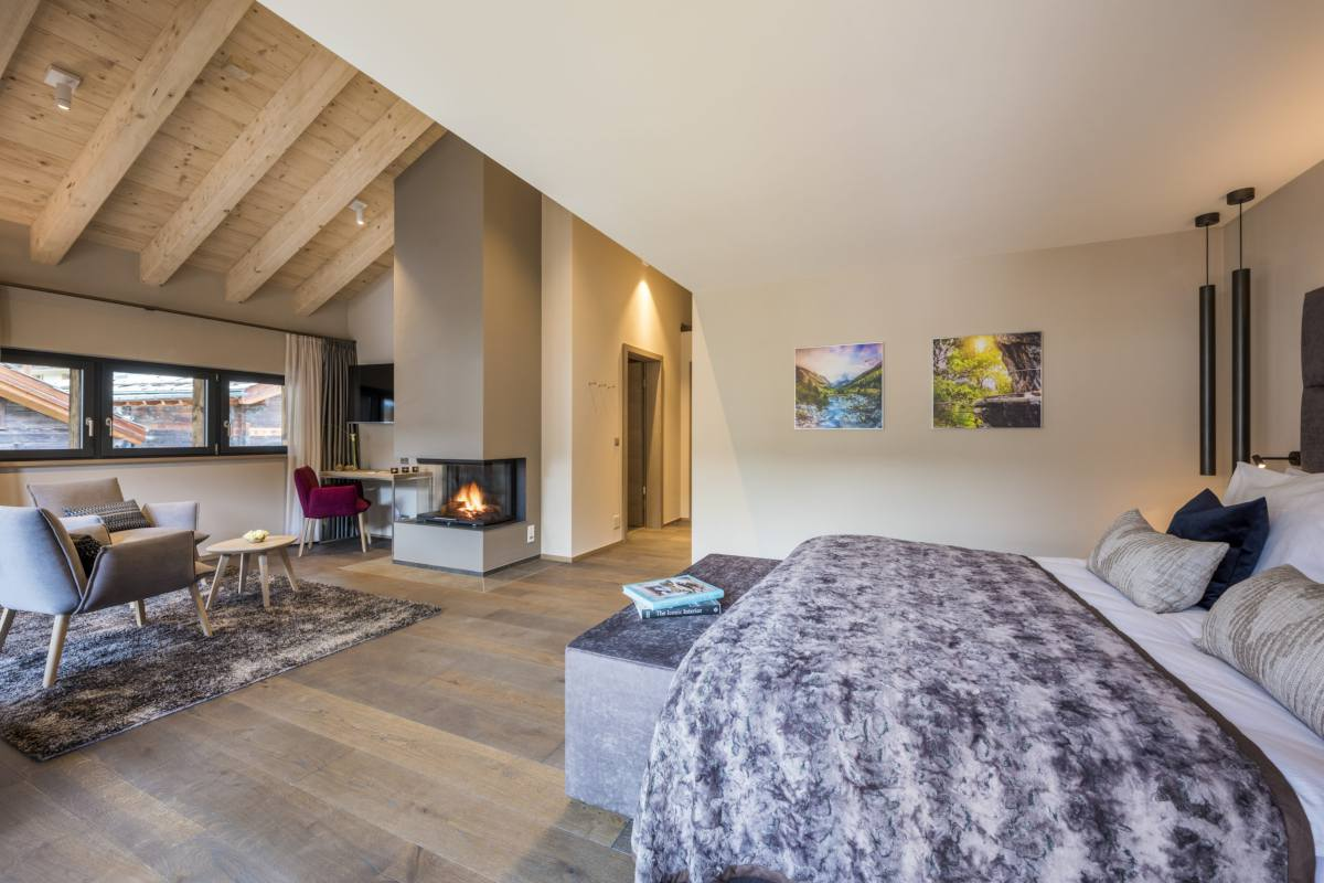 Master bedroom with fireplace and sitting area at Christiania Penthouse in Zermatt