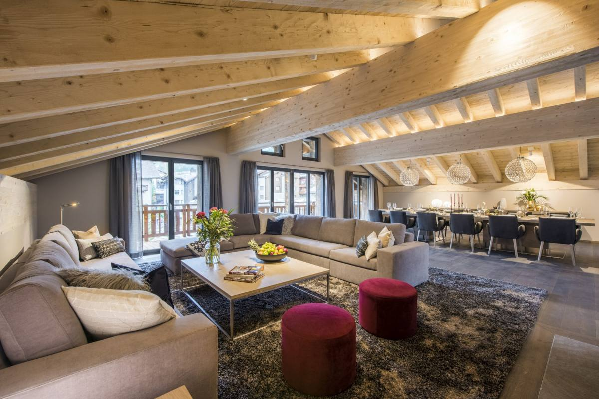 Open-plan living area showing sitting area with dining table on far side at Christiania Penthouse in Zermatt