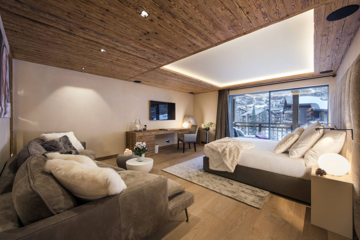 First master bedroom with balcony and sofa at Chalet Elbrus in Zermatt