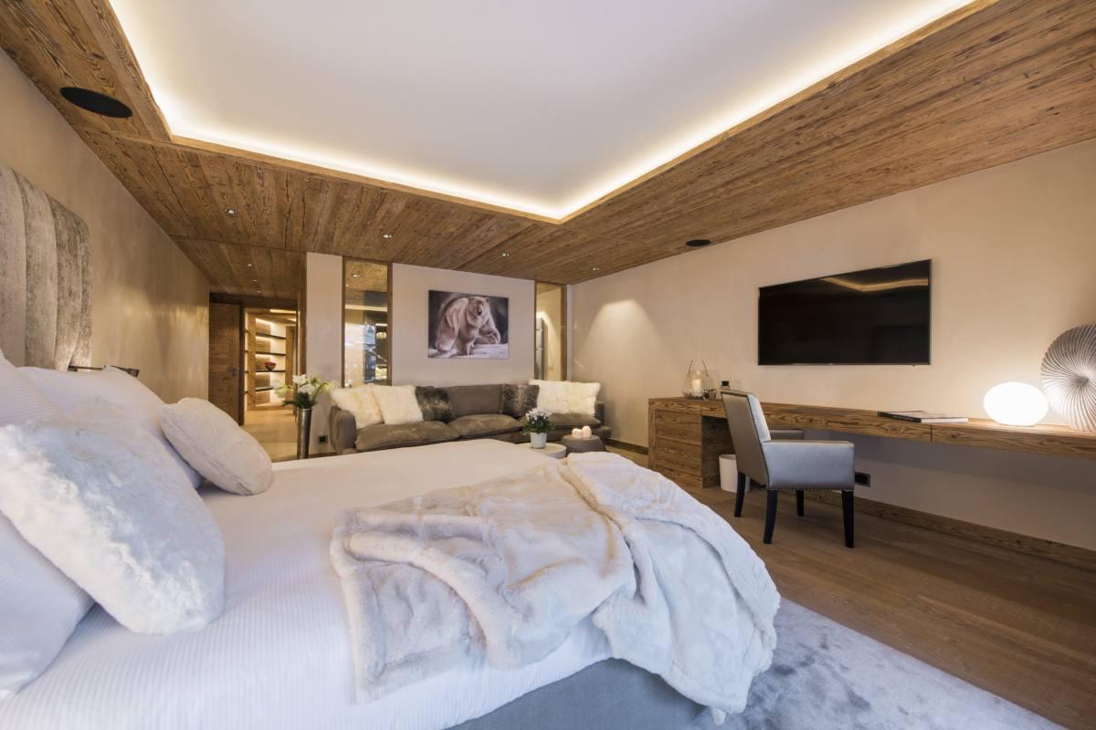 First master bedroom with desk, TV and sofa at Chalet Elbrus in Zermatt