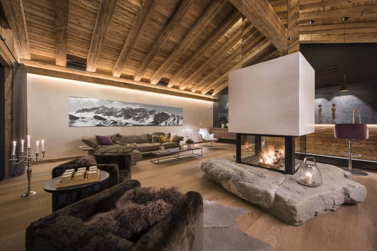 Open-plan living area with island fireplace at Chalet Elbrus in Zermatt