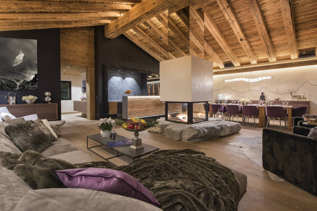 Living and dining room at night at Chalet Elbrus in Zermatt