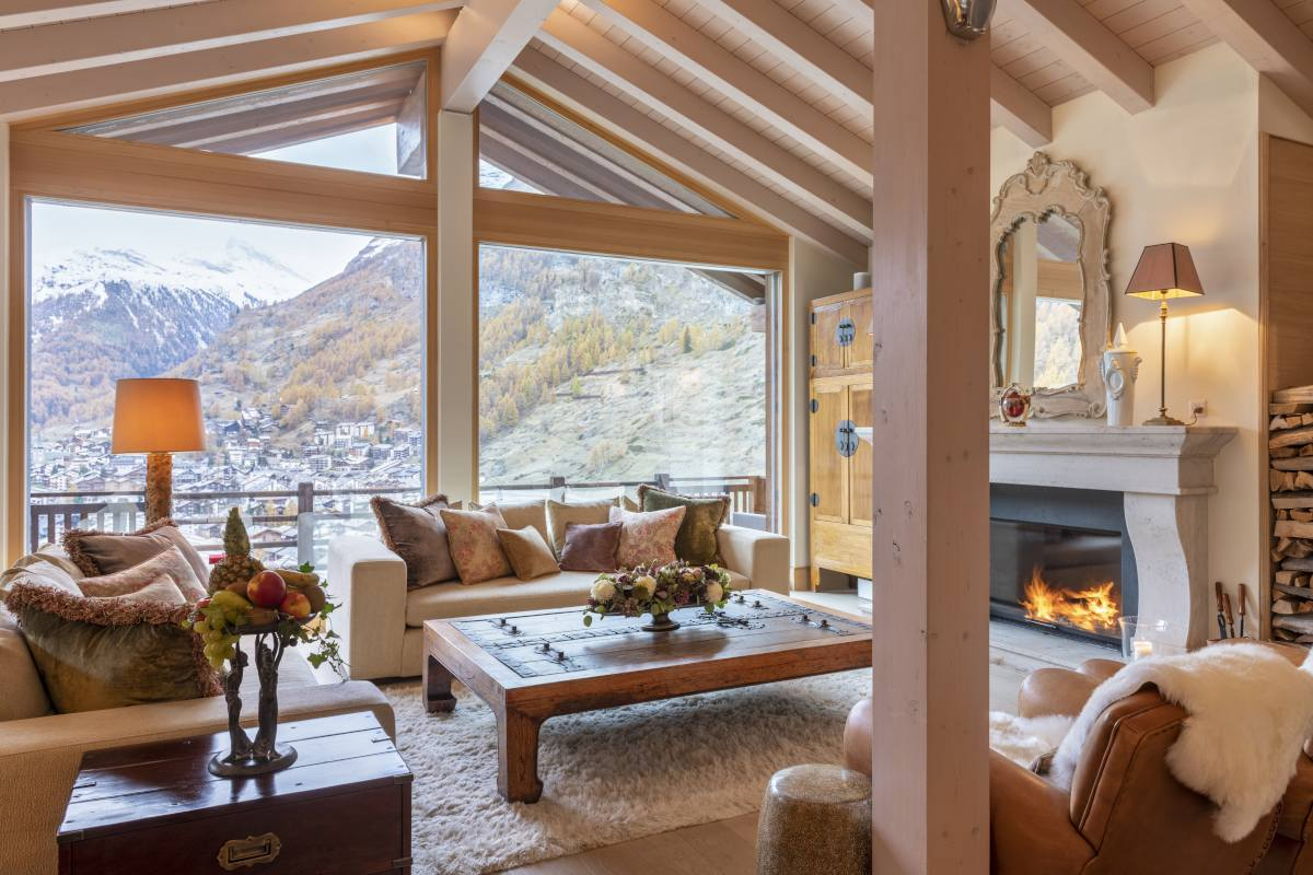 Living room with mountain views and French stone fireplace at Chalet Grace in Zermatt
