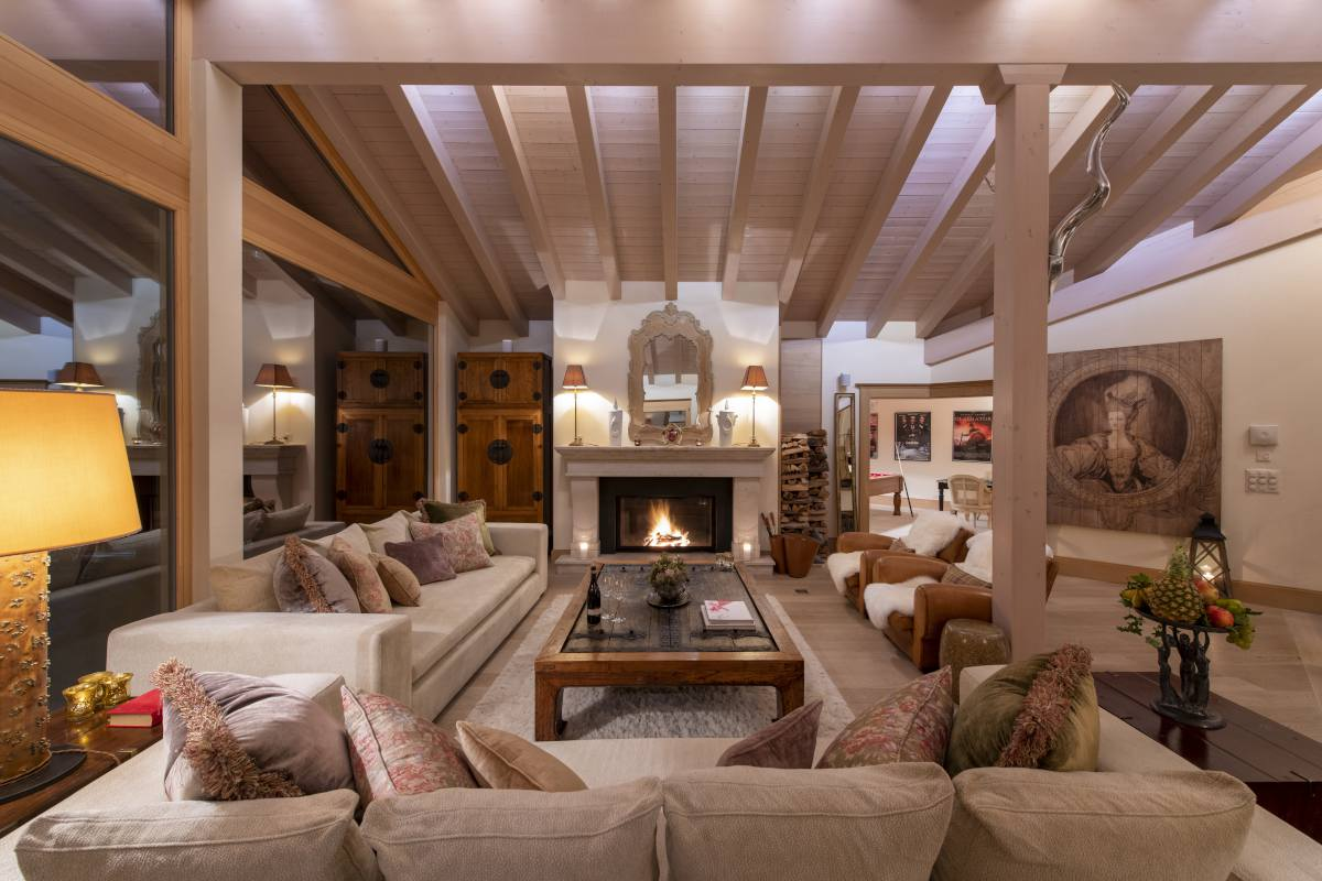 Living room at night with French stone fireplace at Chalet Grace in Zermatt