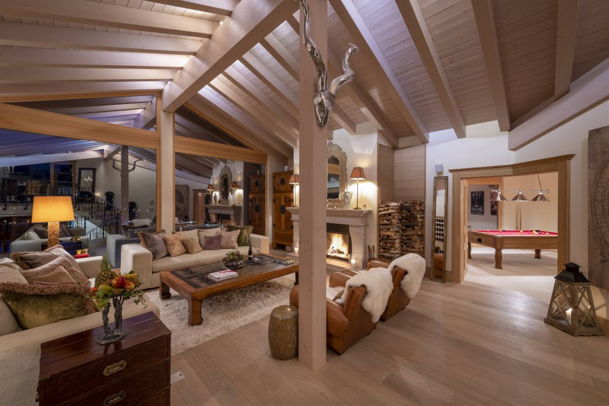 Living room with view into games room at Chalet Grace in Zermatt