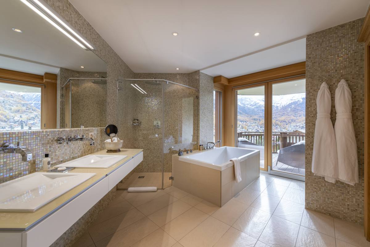 Master bathroom with freestanding bathtub, separate shower and mountain views at Chalet Grace in Zermatt