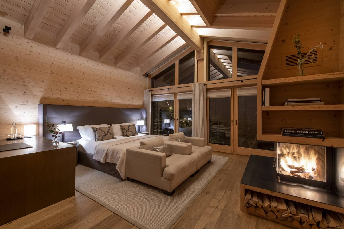 Chevalier master bedroom with fireplace and sitting area at Chalet Maurice in Zermatt