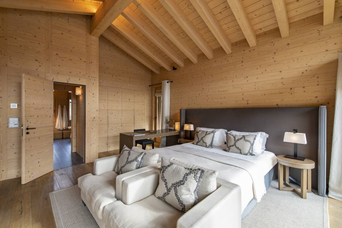 Chevalier master bedroom with seating in front of the fireplace at Chalet Maurice in Zermatt