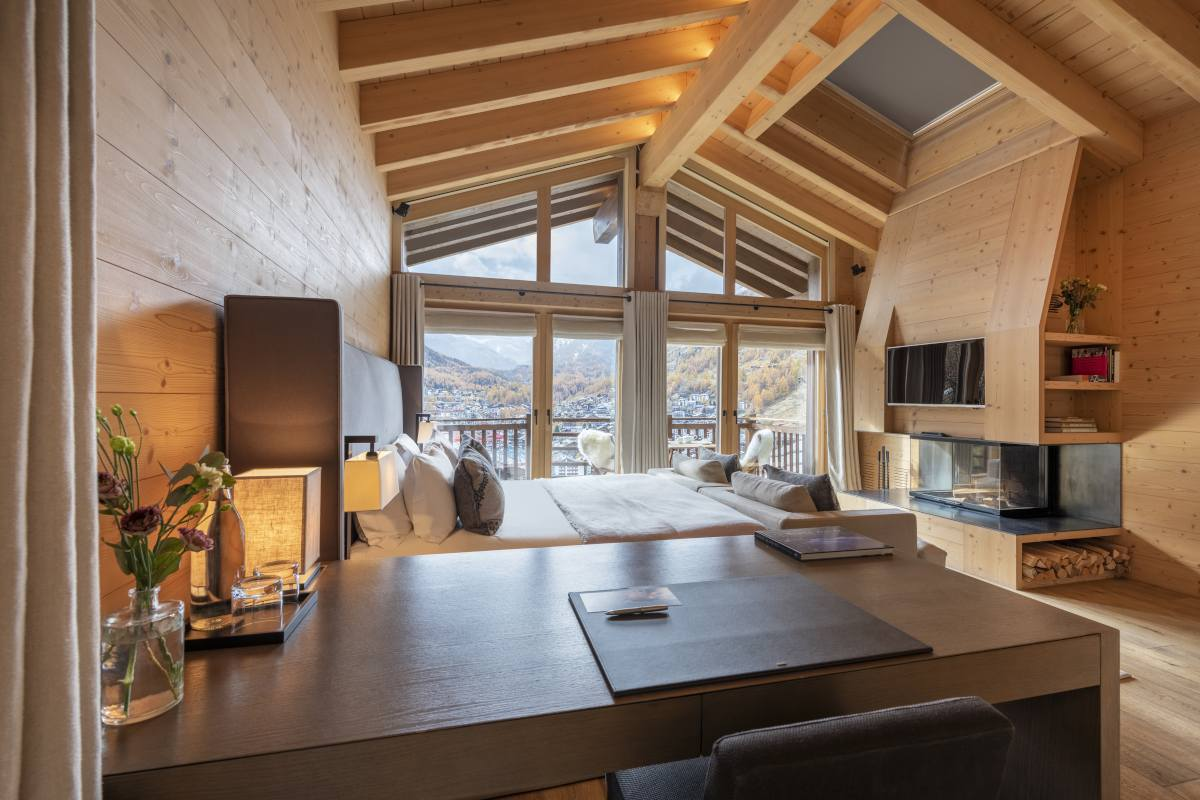 Chevalier master bedroom with fireplace and views at Chalet Maurice in Zermatt
