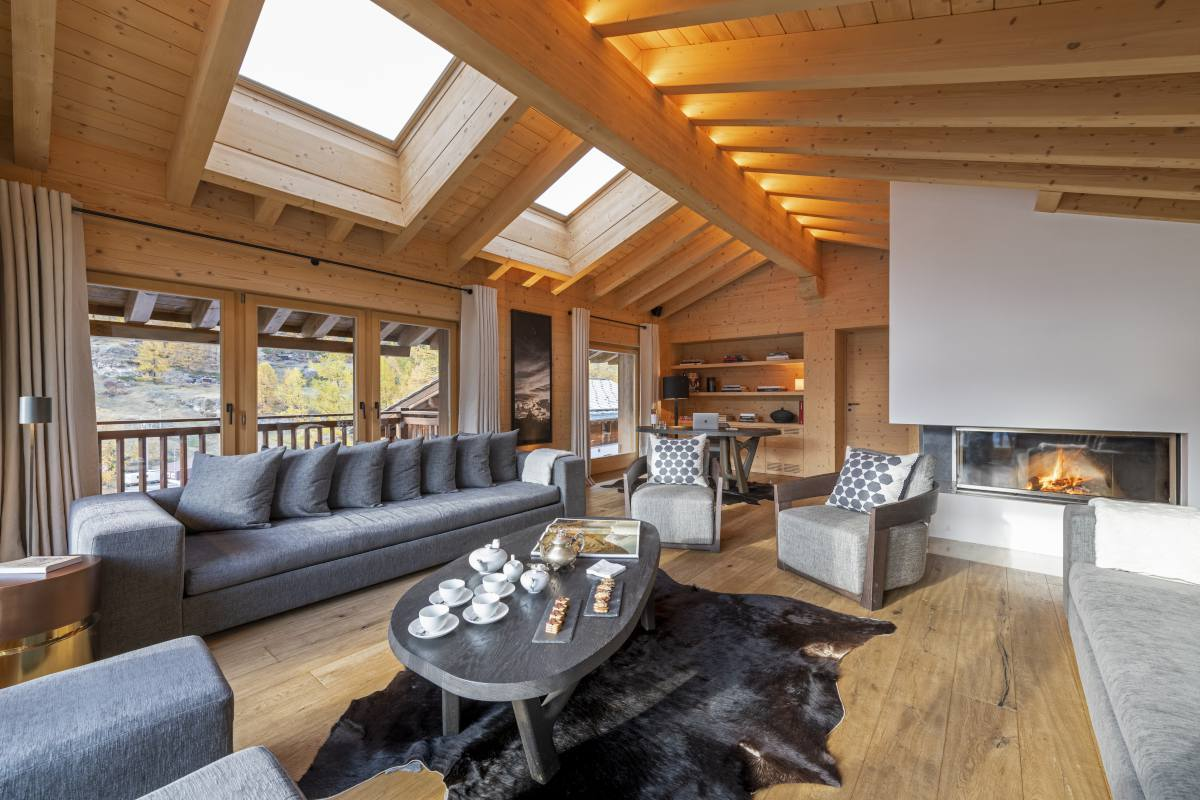 Living room with skylight windows and wood burning fireplace at Chalet Maurice in Zermatt
