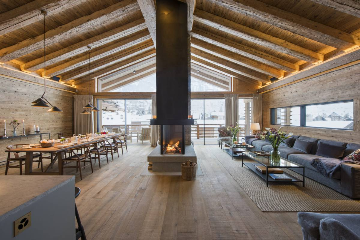 Open-plan living an dining area with double height ceilings and mountain views at Chalet McKinley in Zermatt