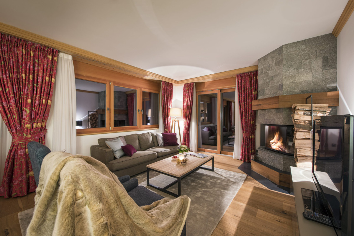 Downstairs living area with open fire at Chalet Shalimar in Zermatt