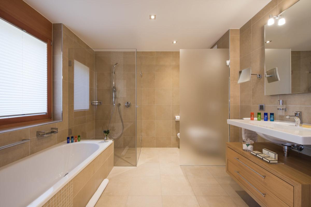 Ensuite bathroom with shower and bathtub at Chalet Shalimar in Zermatt