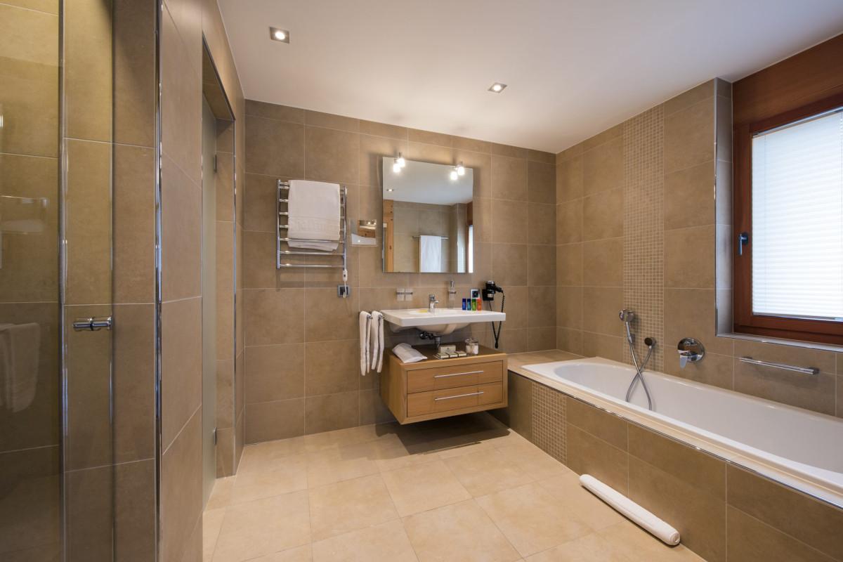 Ensuite bathroom with bath at Chalet Shalimar in Zermatt