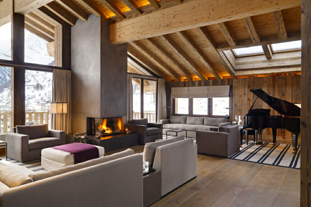 The lounge room with open fire and grand piano at Chalet Les Anges Zermatt