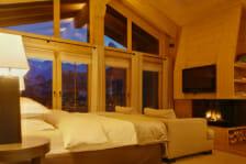 Master bedroom with open fire in Chalet Maurice, Zermatt